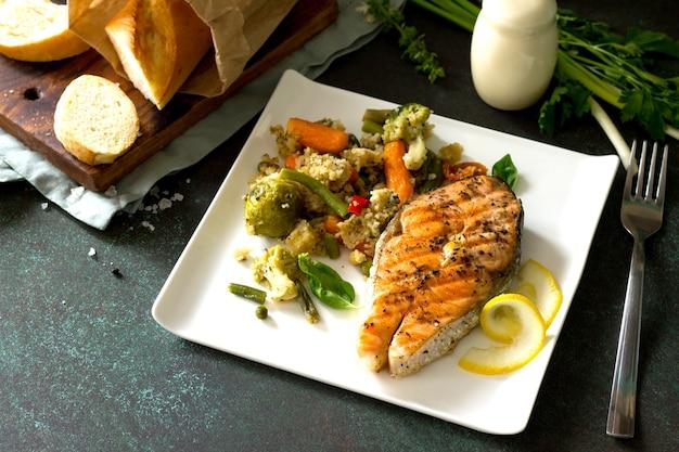 Grillowany stek z łososia z kuskusem i warzywami na kamiennym lub betonowym stole
