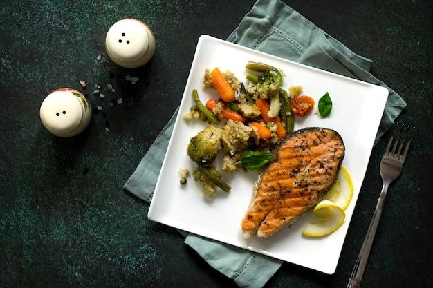 Grillowany stek z łososia z kuskusem i warzywami na kamiennym stole zdrowa żywność widok z góry