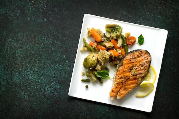 Grillowany stek z łososia z kuskusem i warzywami na kamiennym stole zdrowa żywność
