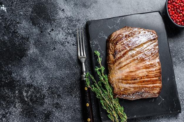 Grillowany stek z mięsa wołowego flanki na marmurowej desce. czarne tło. widok z góry. skopiuj miejsce.