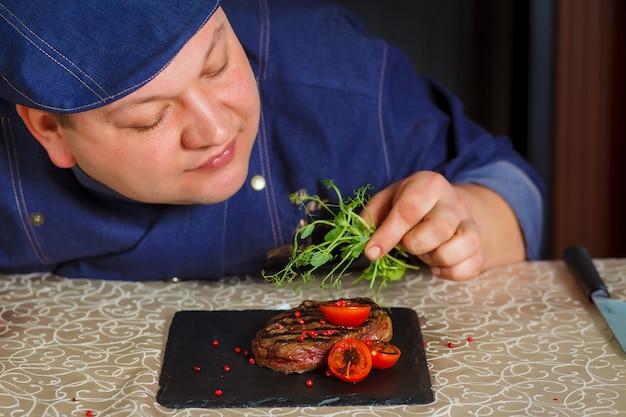 Grillowany stek z mikro-zieleniami i pomidorami na czarnym kwadratowym talerzu. męski ręka szefa kuchni dekoruje niegotowane steki.
