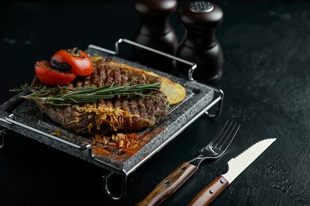 Grillowany stek z nożem i k rzeźbiony na czarnym kamiennym łupku. stek na gorącym marmurowym kamieniu. copyspace, ciemny, moda na jedzenie.