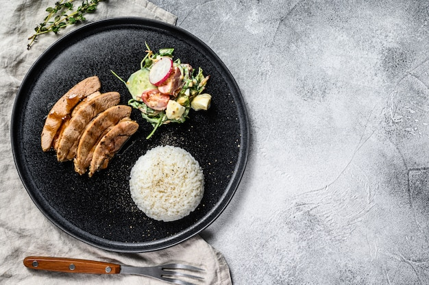 Grillowany stek z piersią kurczaka, przyozdobiony ryżem. widok z góry