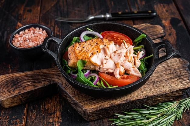 Grillowany stek z polędwicy rybnej z łososia ze świeżą rukolą, awokado i pomidorem na patelni. ciemne drewniane tło. widok z góry.