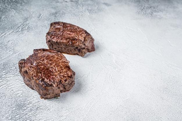 Grillowany stek z polędwicy wołowej mignon lub polędwicy wołowej na stole w kuchni. białe tło. widok z góry. skopiuj miejsce.