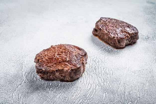 Grillowany stek z polędwicy wołowej mignon lub polędwicy wołowej na stole w kuchni. białe tło. widok z góry.