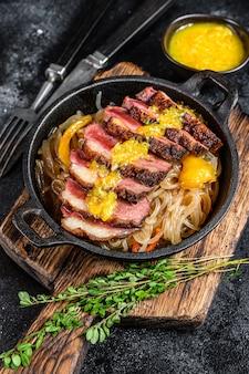 Grillowany stek z polędwicy z piersi kaczki z makaronem i sosem mandarynkowym. czarne tło. widok z góry.