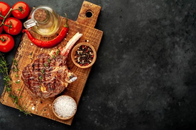 Grillowany stek z przyprawami, tymianek na kamiennym tle. z miejsca na kopię tekstu