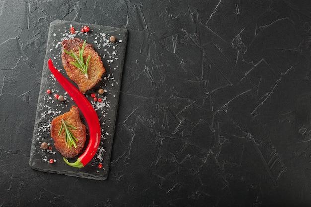 Grillowany stek z rozmarynem i papryką chili na ciemnym kamieniu