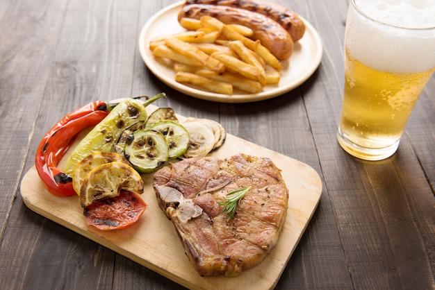Grillowany stek z sałatką, piwem i frytkami kiełbasą na drewnianym bakcground.