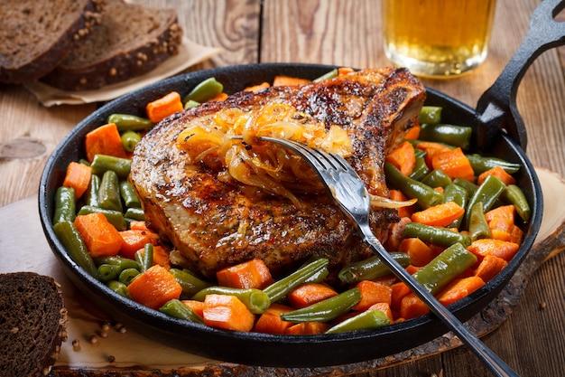 Grillowany stek z wieprzowiny ze smażoną cebulą, zieloną fasolką i marchewką na patelni na naturalnym drewnianym tle.