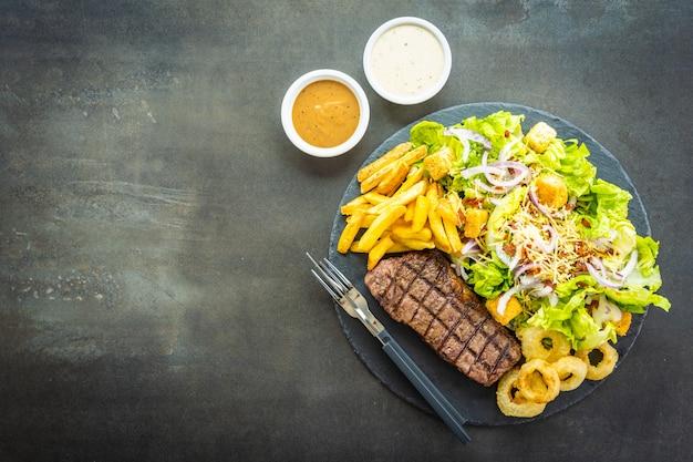 Grillowany stek z wołowiny z frytkami z cebulką