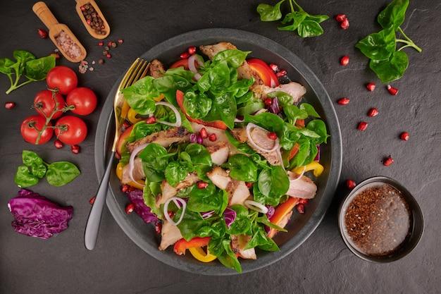 Grillowany stek ze świeżymi warzywami, słodką papryką, pomidorami, czerwoną cebulą, różowym pieprzem i przyprawami. domowe smaczne jedzenie. koncepcja smacznego i zdrowego posiłku. czarna powierzchnia kamienia. stek wieprzowy z surówką