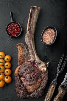 Grillowany suchy zestaw mięsa wołowego tomahawk steak, na czarnym kamiennym tle, płaski widok z góry