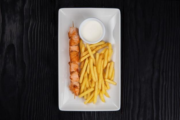 Grillowany szaszłyk rybny z łososia ze smażonymi ziemniakami i sosem na białym talerzu na czarnym drewnianym tle