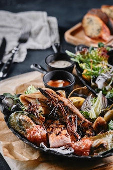 Grillowany talerz z owocami morza. różne pyszne owoce morza z grilla z warzywami. grillowane mieszane dranie z sosem pieprzowym i warzywami. niebieskie tło