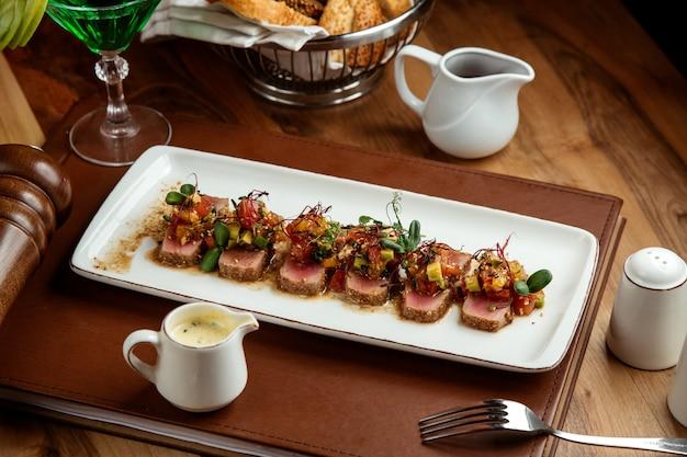 Grillowany tuńczyk z pomidorami z awokado, sosem sezamowym, chlebem i szklanką lemoniady tarhun na stole