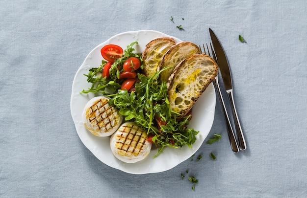 Grillowany włoski ser tomino podany na stole z sałatką z rukoli i świeżym domowym chlebem ciabatta i pomidorem na świątecznym obrusie z niebieskiego lnu. letnie menu