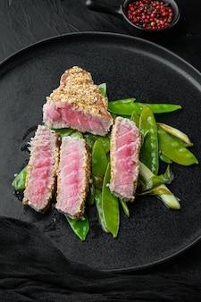Grillowany zestaw stek z tuńczyka ahi z dymką i groszkiem cukrowym, na talerzu, na czarnym kamiennym tle