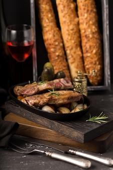Grilluj stek wieprzowy na starej rustykalnej drewnianej desce do krojenia w wiejskiej kuchni z czerwonym winem i francuską bagietką na drewnianej czarnej ścianie