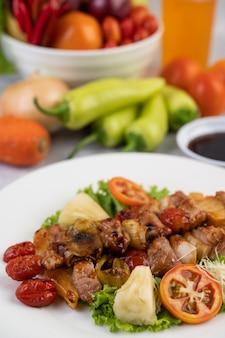 Grilluj z różnymi mięsami, w komplecie z pomidorami i papryką na białym talerzu.