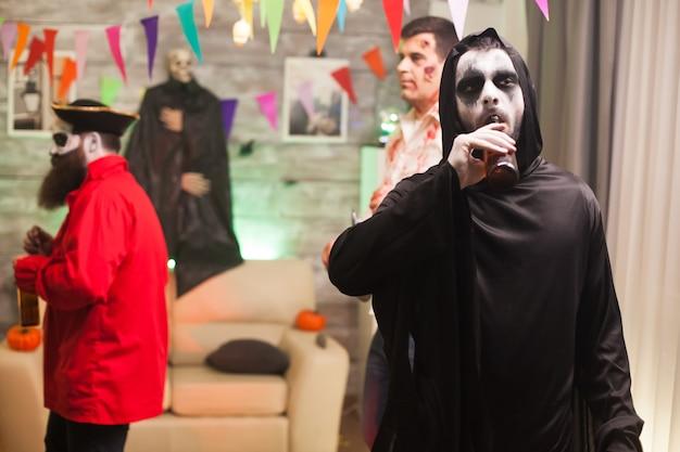 Grim reaper cieszący się piwem podczas obchodów halloween. straszny mężczyzna.