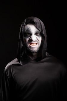 Grim reaper z przerażającą twarzą na białym tle na czarnym tle. zła twarz.