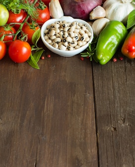 Groch czarnooki w misce i warzywa na drewnie z bliska