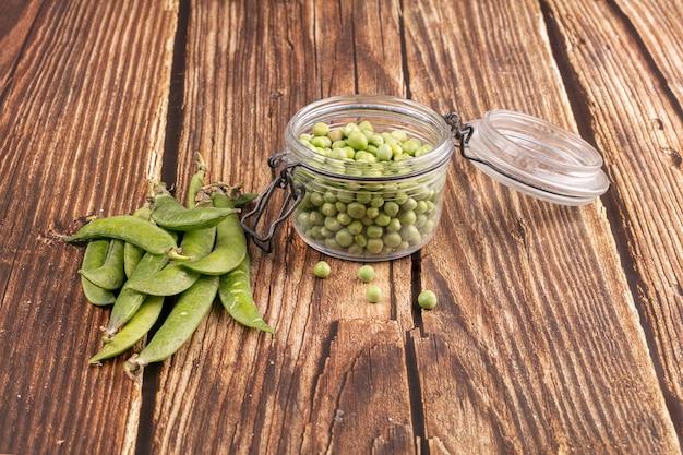 Groch łuskany w szklanym słoju ze strączkami na boku na drewnianym stole