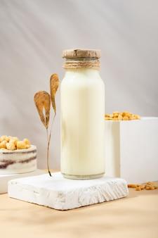 Groch warzywny w butelce i ciecierzyca w ręcznie robionej ceramicznej misce na białym podium, cokół na beżowym tle. cienie. suche liście. bezglutenowy, bezlaktozowy produkt wegański. nowoczesny. skopiuj miejsce