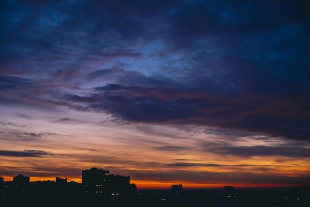 Gród z żywym ciepłym świtem. niesamowite dramatyczne błękitne fioletowe pochmurne niebo nad ciemnymi sylwetkami budynków miasta. pomarańczowe światło słoneczne. atmosferyczne tło wschodu słońca w pochmurnej pogodzie. skopiuj miejsce