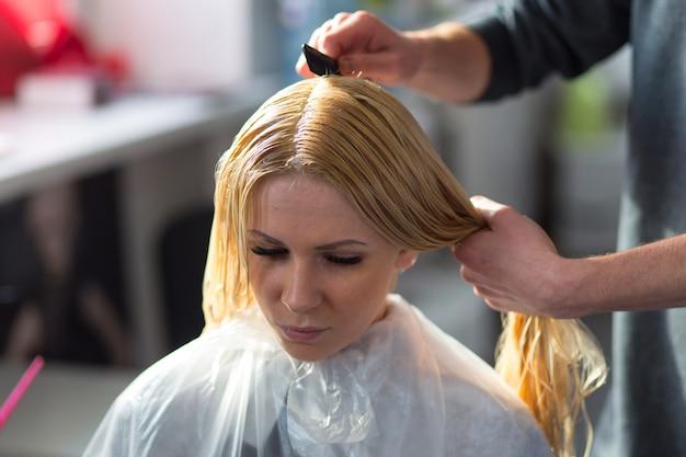 Grodno, białoruś - 20 października 2016: technolog marki keune artem raychuk farbuje włosy modelu na warsztatach reklamowych z udziałem w salonie kosmetycznym kolibri.