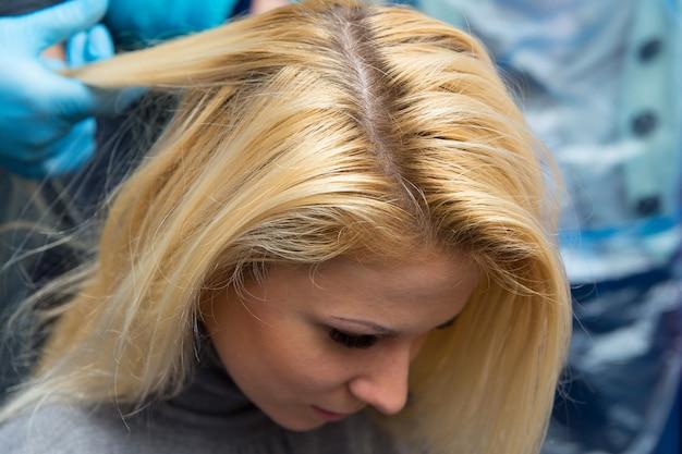 Grodno, białoruś - 20 października 2016: uczestnicy seminarium farbują włosy modelu na warsztatach reklamowych marki keune w salonie kosmetycznym kolibri.