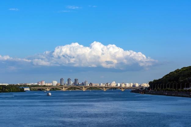 Gromada chmur nad miastem na tle czystego nieba i rzeki.