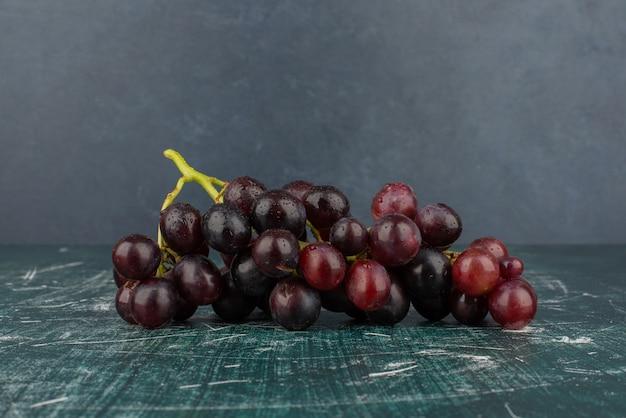 Grono czarnych winogron na marmurowym stole.