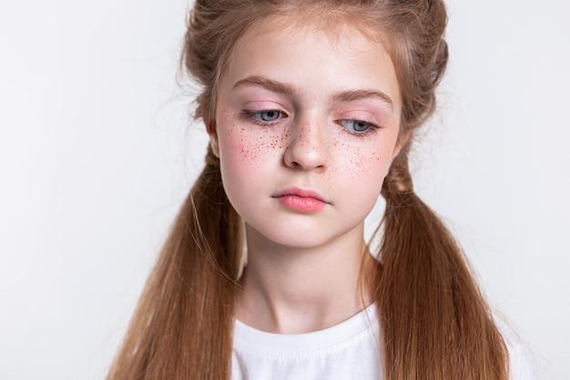 Grono piegów. atrakcyjna młoda dziewczyna jest smutna i nudna, patrząc w dół z niebieskimi oczami