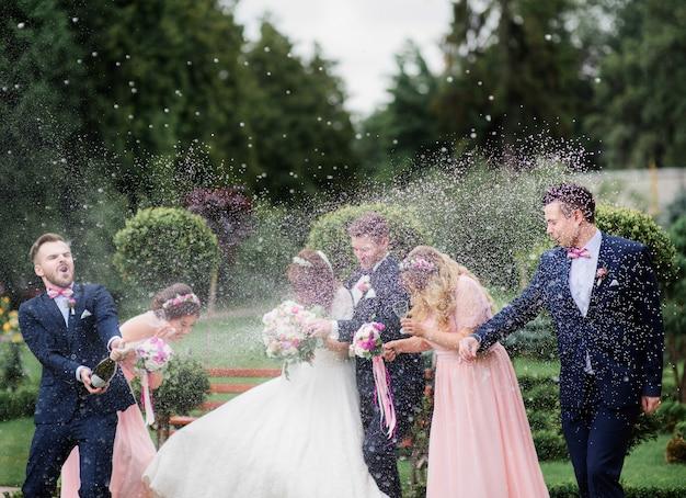 Groomsman otwiera butelkę szampana przed nowożeńcami stojącymi w parku