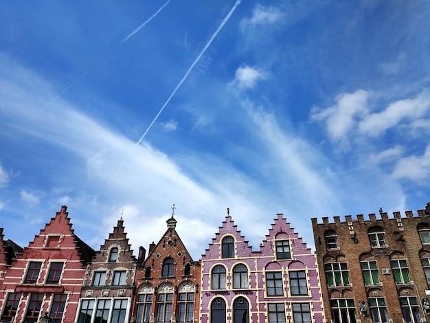 Grote markt pod błękitnym niebem i światłem słonecznym w brugii w belgii