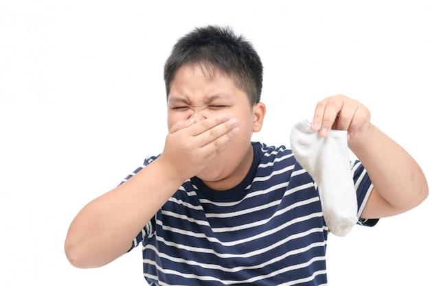 Gruba chłopiec trzyma brudne śmierdzące skarpety na białym tle