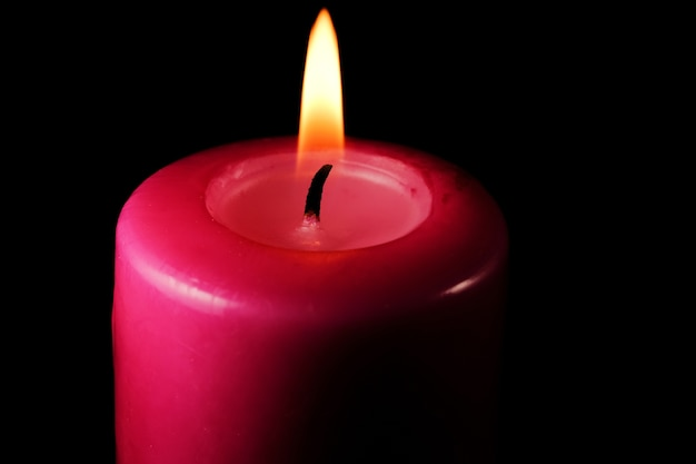Gruba czerwona pamiątkowa czerwona świeca płonąca na czarnym tle
