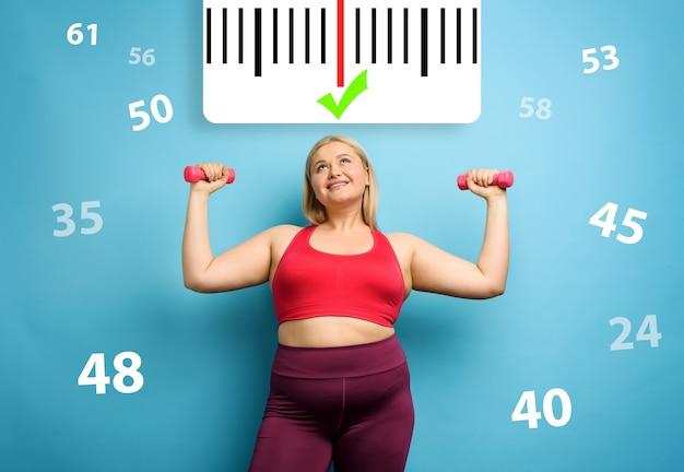 Gruba dziewczyna ćwiczy w domu na siłowni z zadowolonym wyrazem twarzy, ponieważ zmniejsza wagę. niebieskie tło
