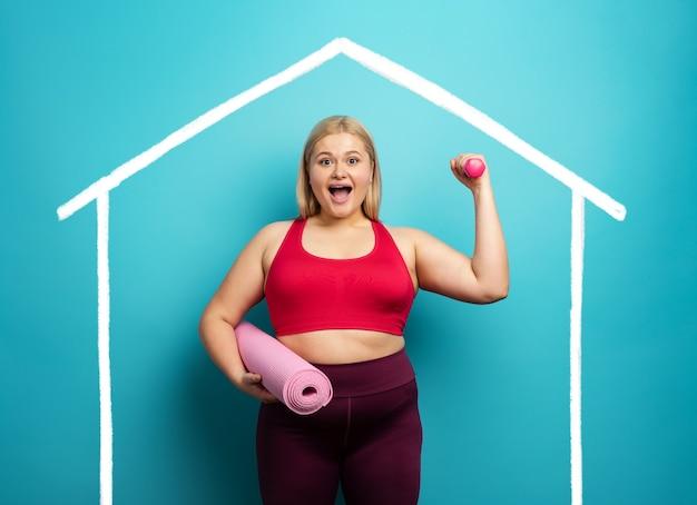Gruba dziewczyna robi siłownię w domu. zadowolony wyraz