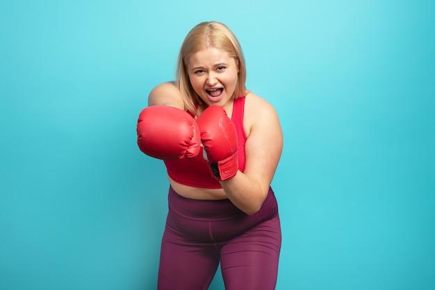 Gruba dziewczyna w sali fitness uprawia boks