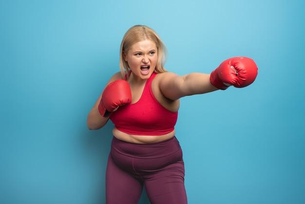 Gruba dziewczyna w siłowni robi boks.