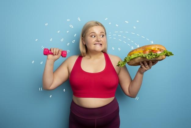 Gruba kobieta ćwiczy na siłowni i chce zjeść kanapkę.