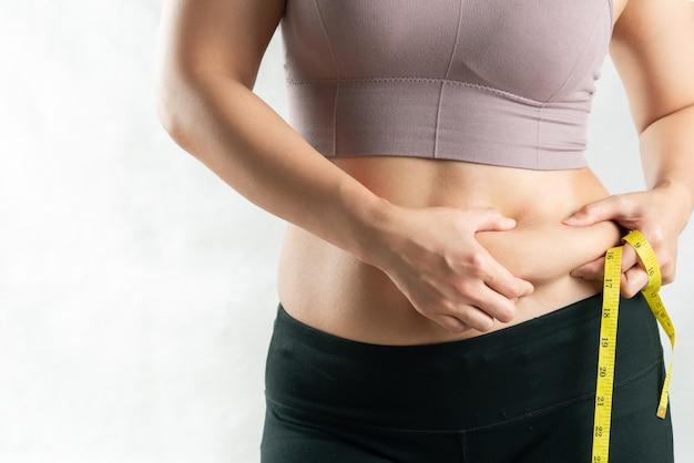 Gruba kobieta, gruby brzuch, pulchna, otyła kobieta ręka trzyma nadmierny tłuszcz z brzucha z miarką, koncepcja stylu życia diety kobiety