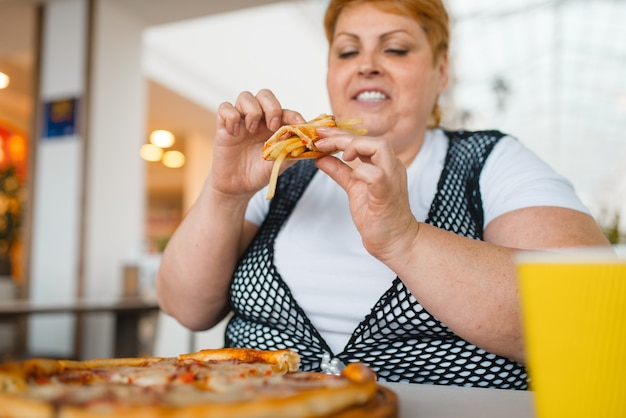 Gruba kobieta jedzenie pizzy z frytkami w restauracji centrum handlowego, niezdrowe jedzenie. kobieta z nadwagą przy stole ze śmieciowym obiadem, problem z otyłością