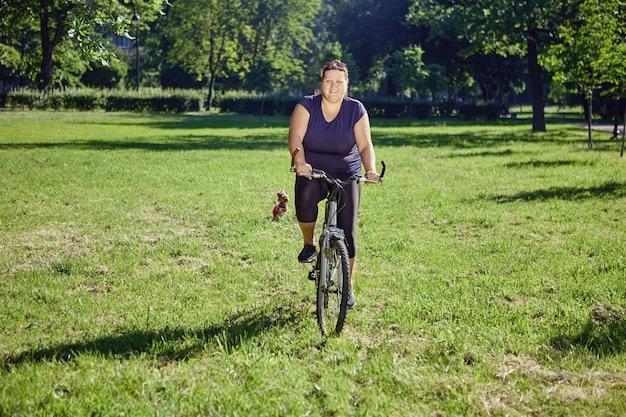 Gruba kobieta jeździ rowerem w parku koncepcja pozytywnego ciała i zdrowego stylu życia