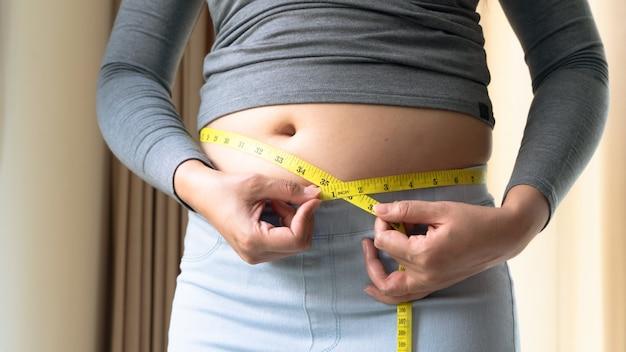 Gruba kobieta ręka trzyma taśmę pomiarową na jej tłuszczu z brzucha. kobieta dieta styl życia i koncepcja budowy mięśni.