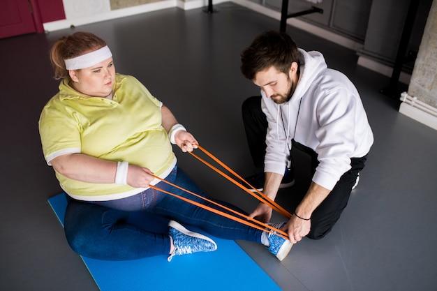 Gruba kobieta rozciągająca się w klasie fitness